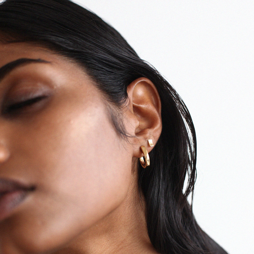BAR Jewellery Sustainable Taper and Coppia Stud Earrings In Gold, Worn On Ear
