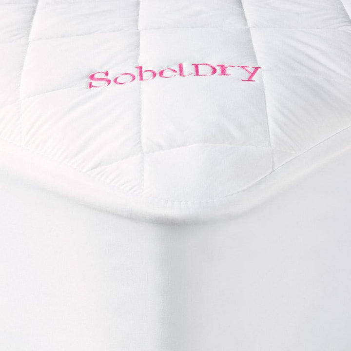 Princess Mattress Pad covering bed showing corner with pink SobelDry logo