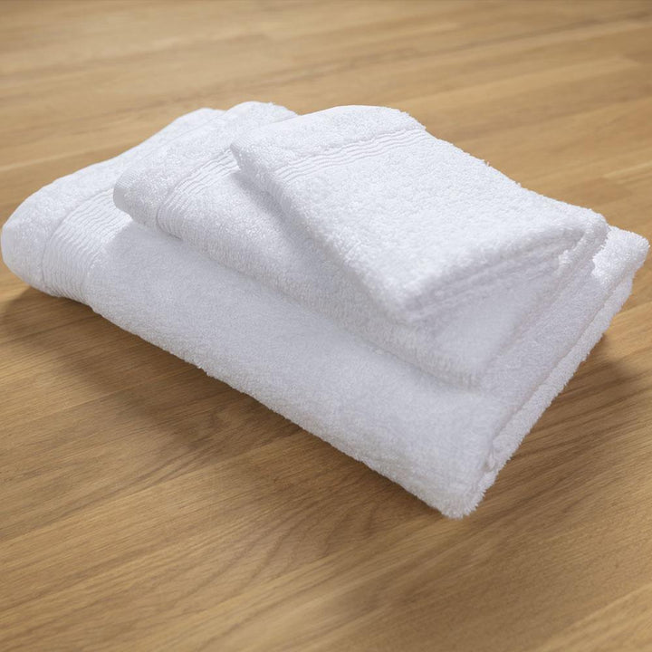 Bath towel, hand towel, and washcloth stacked on wood table