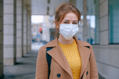 A woman wearing a face mask and a brown coat