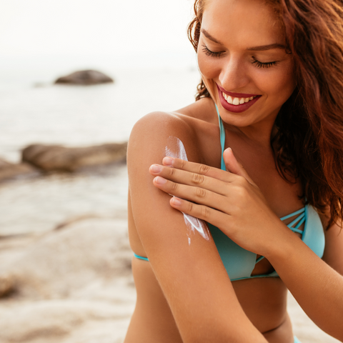 A woman applying sunscreen on her arm.