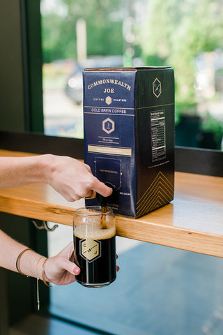 CWJ Boxed Cold Brew pouring into CWJ branded glass