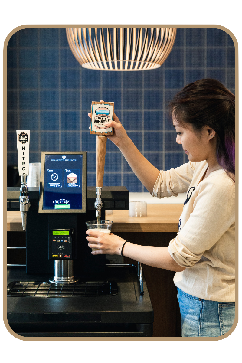 Woman dispensing kombucha from a kegerator vending machine