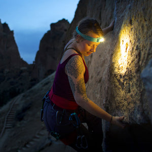 Girl climbing outside on rock wall using teale BioLite 330 headlamp