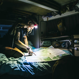 person in van reading map in dark with biolite 330 headlamp on