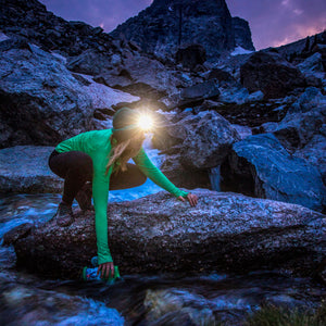 woman climbing outside in dark with biolite 330 headlamp