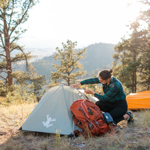 Green Bivy Tent with Rain Fly and woman standing next to the tent in the mountains