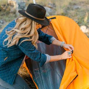 Orange Bivy Tent woman pulling back the rain fly