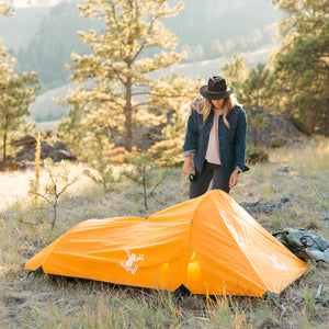 Orange Bivy Tent with Rain Fly and woman standing next to the tent in the mountains
