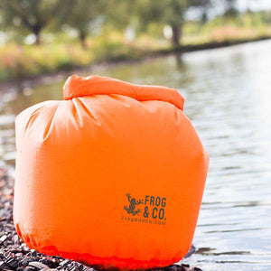 Orange Lightweight Dry Bag Full next to water