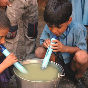 Kids using LifeStraw Personal Water Filters in bowl of dirty water