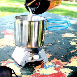 Pocket Stove being used outside with water pouring out into camp cup