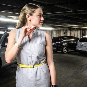 Woman in underground garage looking over her shoulder with orange scream whistle in hand