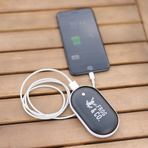 Electric Hand Warmer charging cell phone on table