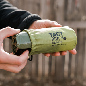 outdoor green bivy in hand taking out of bag