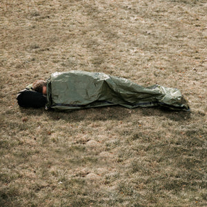 outdoor man in green bivy on ground