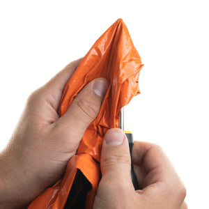 orange bivy in hand with screw driver trying to pierce through