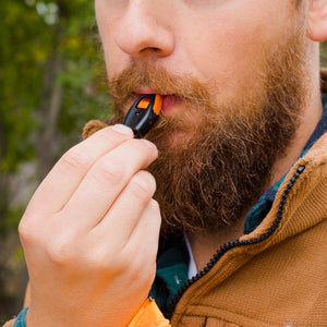 Man using scream whistle that is attached to lighter lanyard