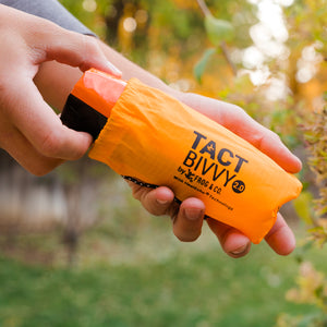 outdoor orange bivy in hand taking out of bag
