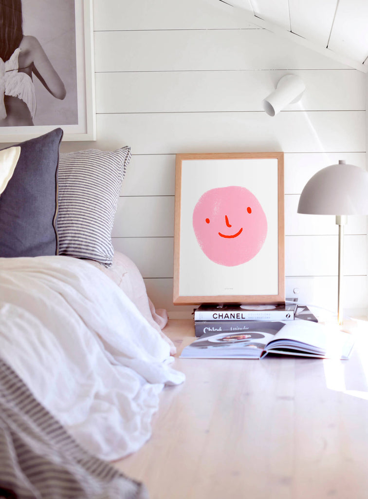 pink emoji poster with smiley face hanging in women bedroom