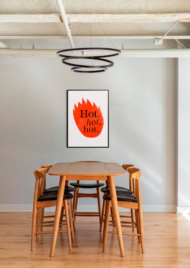 trendy graphic wall art print featuring red flames and hand lettered typography saying hot, hot, hot, and hanging above a table in a minimalist industrial dining room