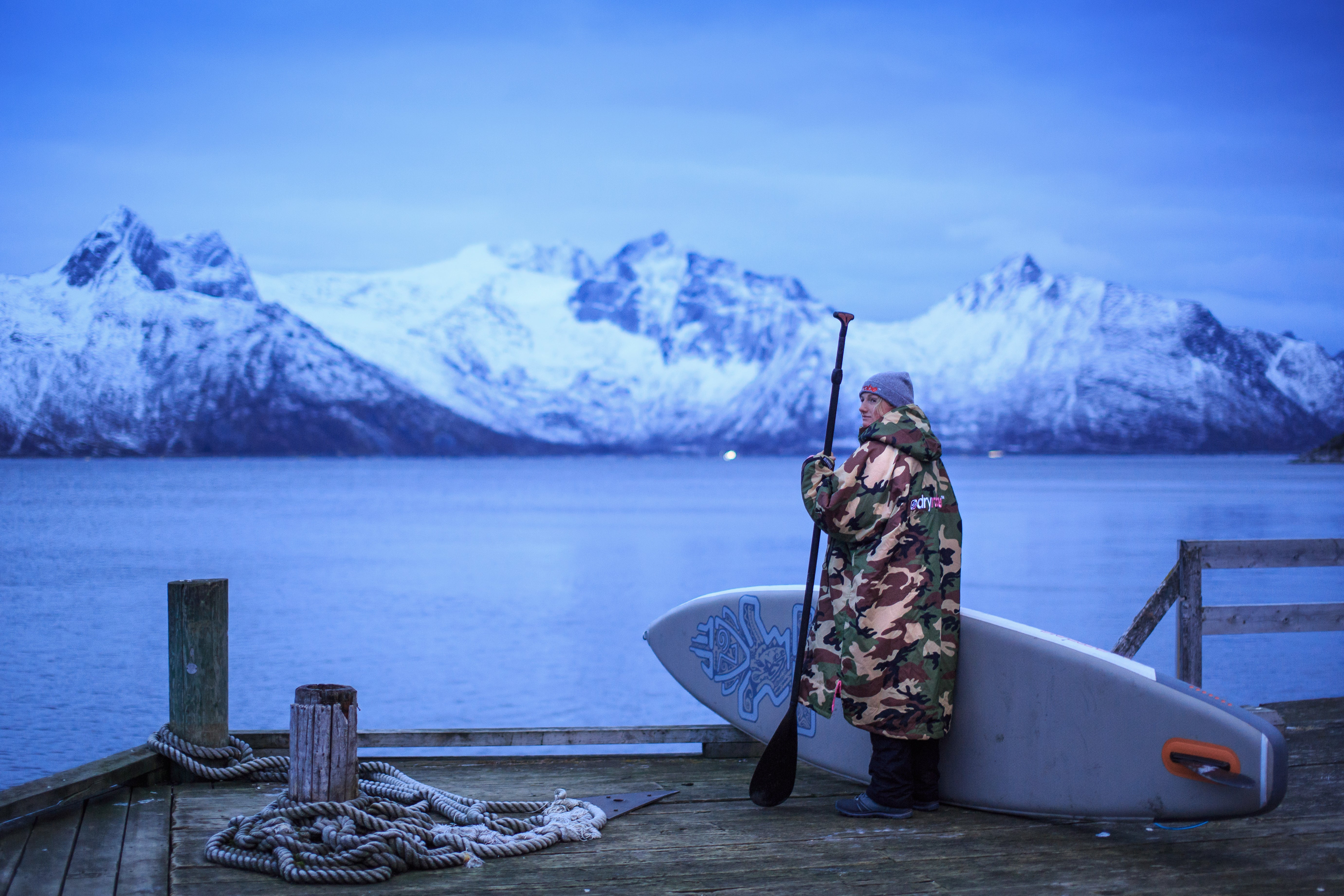 Cal Major standing by a Fjord in Norway in a dryrobe, holding a stand up paddleboard