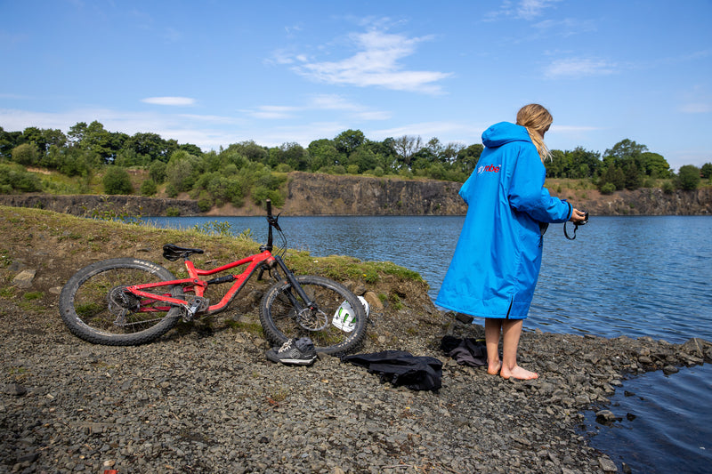 Joanna Shimwell standing by a lake in her cobalt blue dryrobe advance