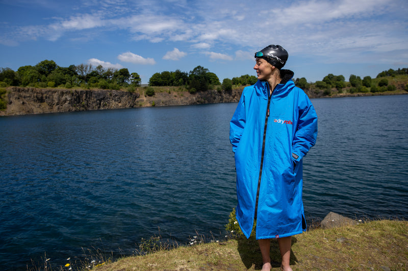 Joanna Shimwell stood by a lake in her dryrobe Advance and swim cap