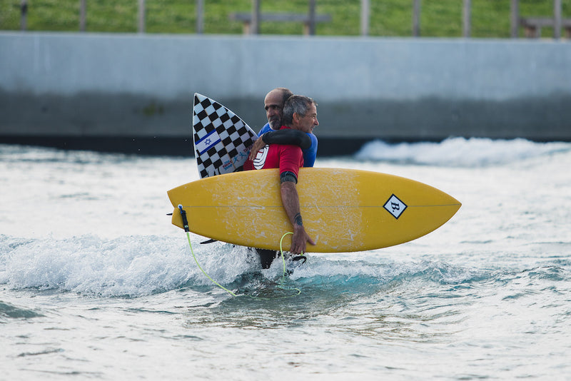 Pegleg hugging a competitor during the English Adaptive Surf Open at The Wave in Bristol