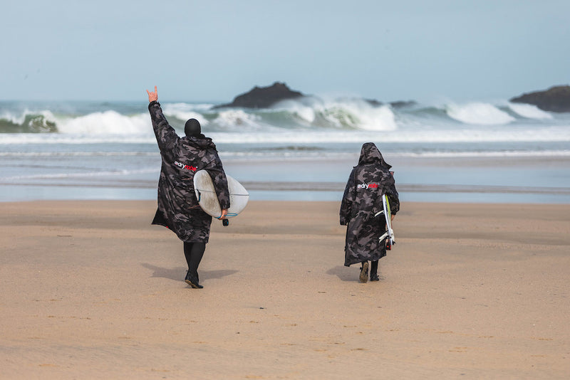 Ben and Lukas Skinner holding surfboards and walking towards the sea