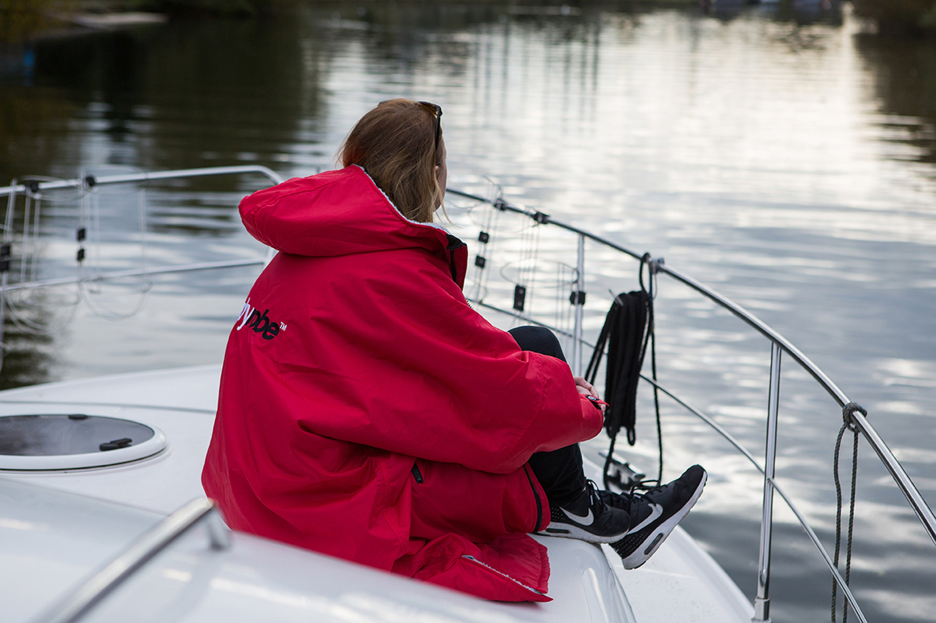 Woman sat on a boat in a dryrobe