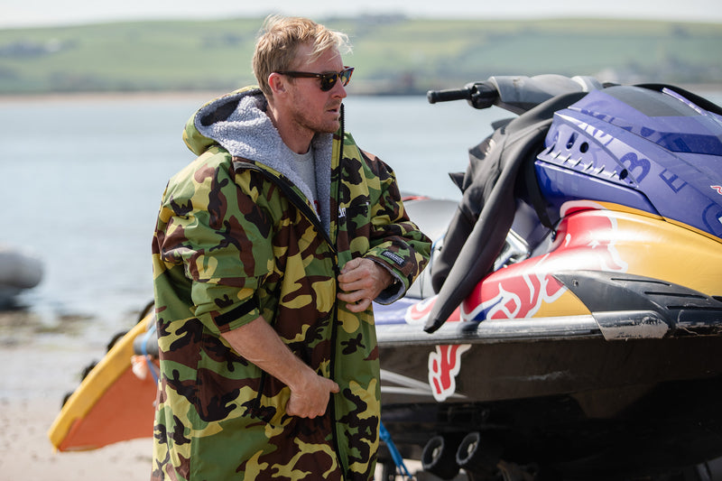 Andrew Cotton wearing a camo dryrobe Advance on the beach next to a jet ski