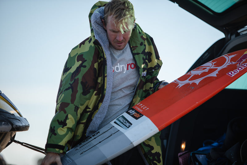 Andrew Cotton taking a surfboard out of the back of his car