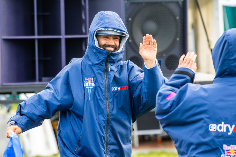 Two cliff divers high-fiving at the Red Bull Cliff Diving World Series wearing dryrobe® Advances