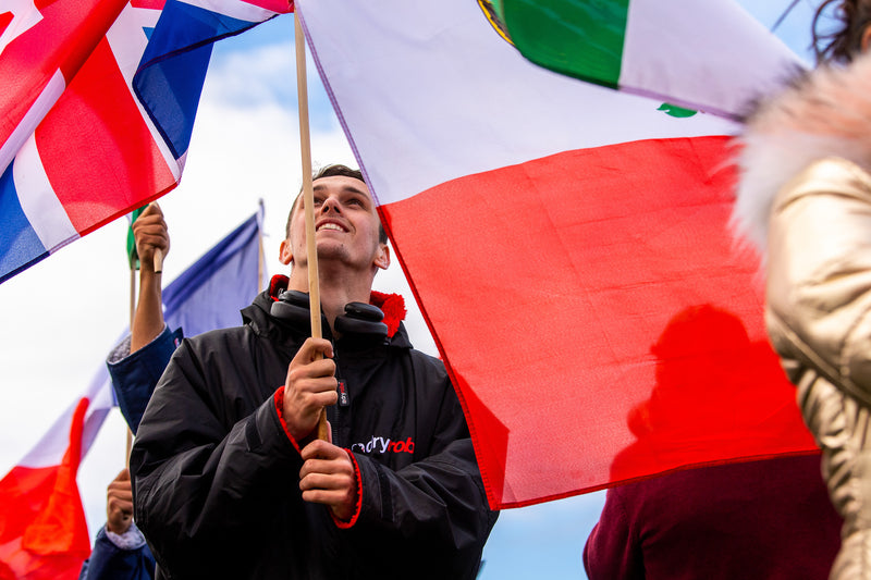 Aidan Heslop at the Red Bull Cliff Diving World Series 2021 holding a flag and wearing a dryrobe® Advance
