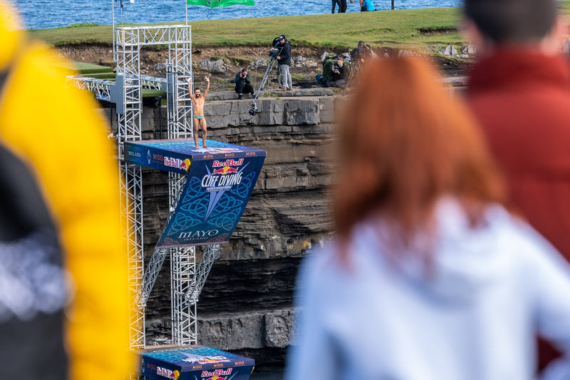 Cliff diver on the diving board with hands raised at the Red Bull Cliff Diving World Series