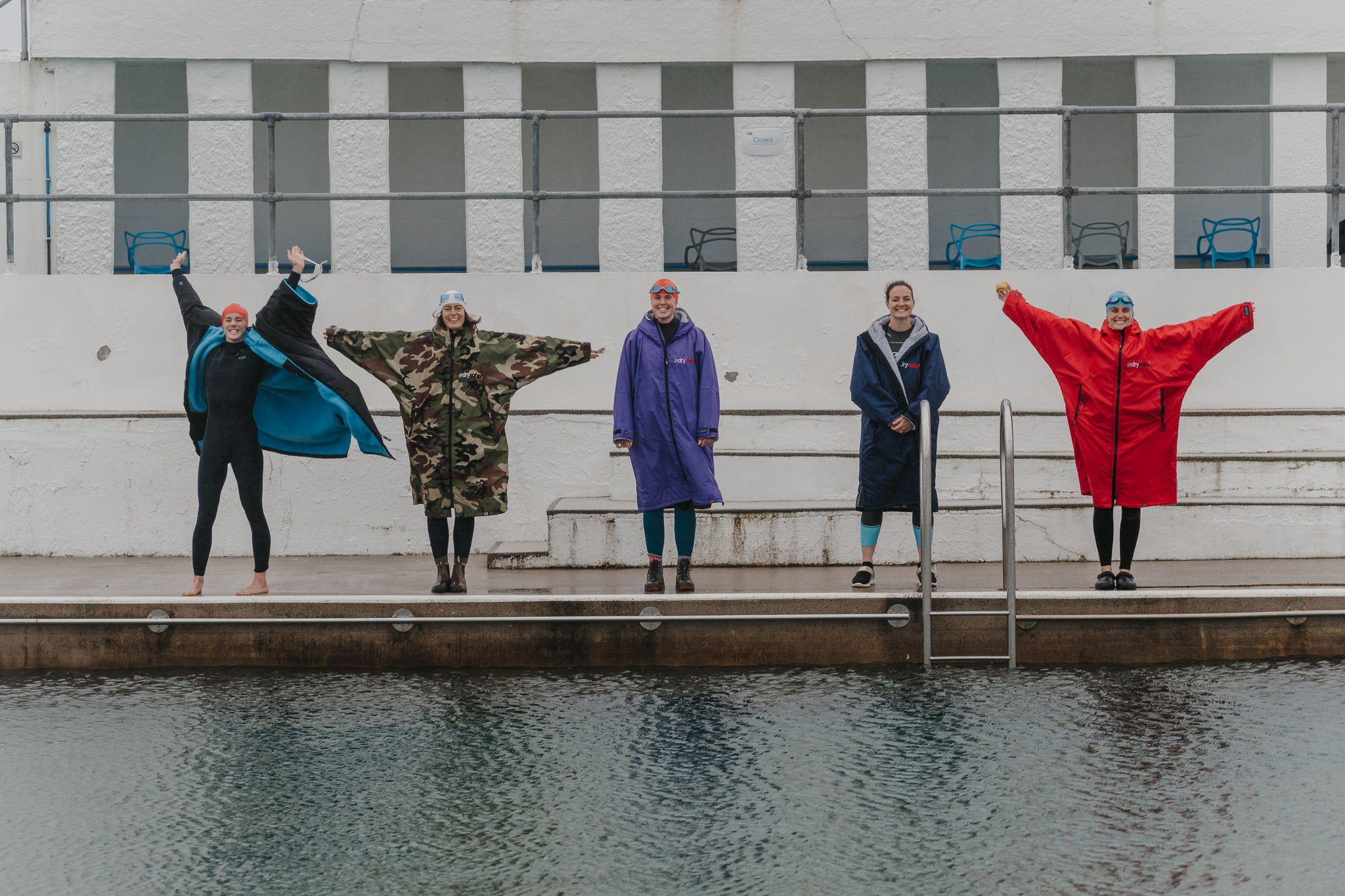 Keri-annne Payne, Lucy Campbell, Sophie Hellyer, Grace Kingswell and Anna Blackwell standing by the pool in their dryrobes