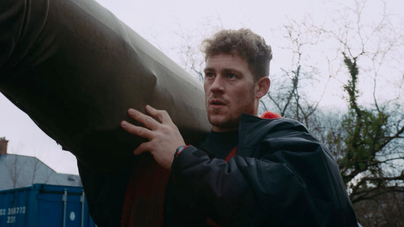 Jack Eyers carrying his canoe on his shoulder outside