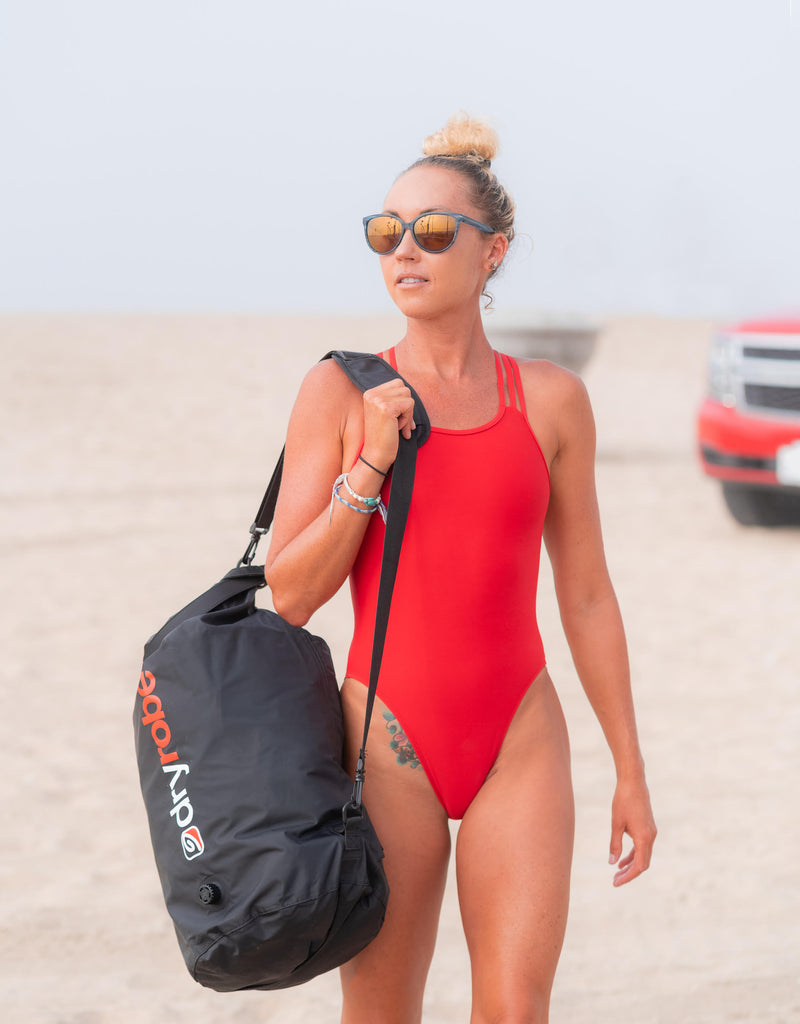 Swimmer Lexie Kelly wearing a red swim suit and carrying a dryrobe travel compression bag