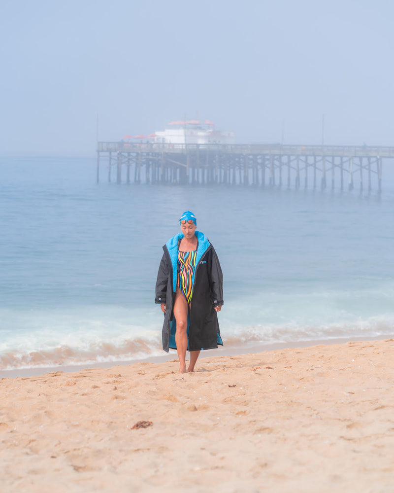 Swimmer Lexie Kelly walking on the beach in swim wear and a dryrobe changing robe