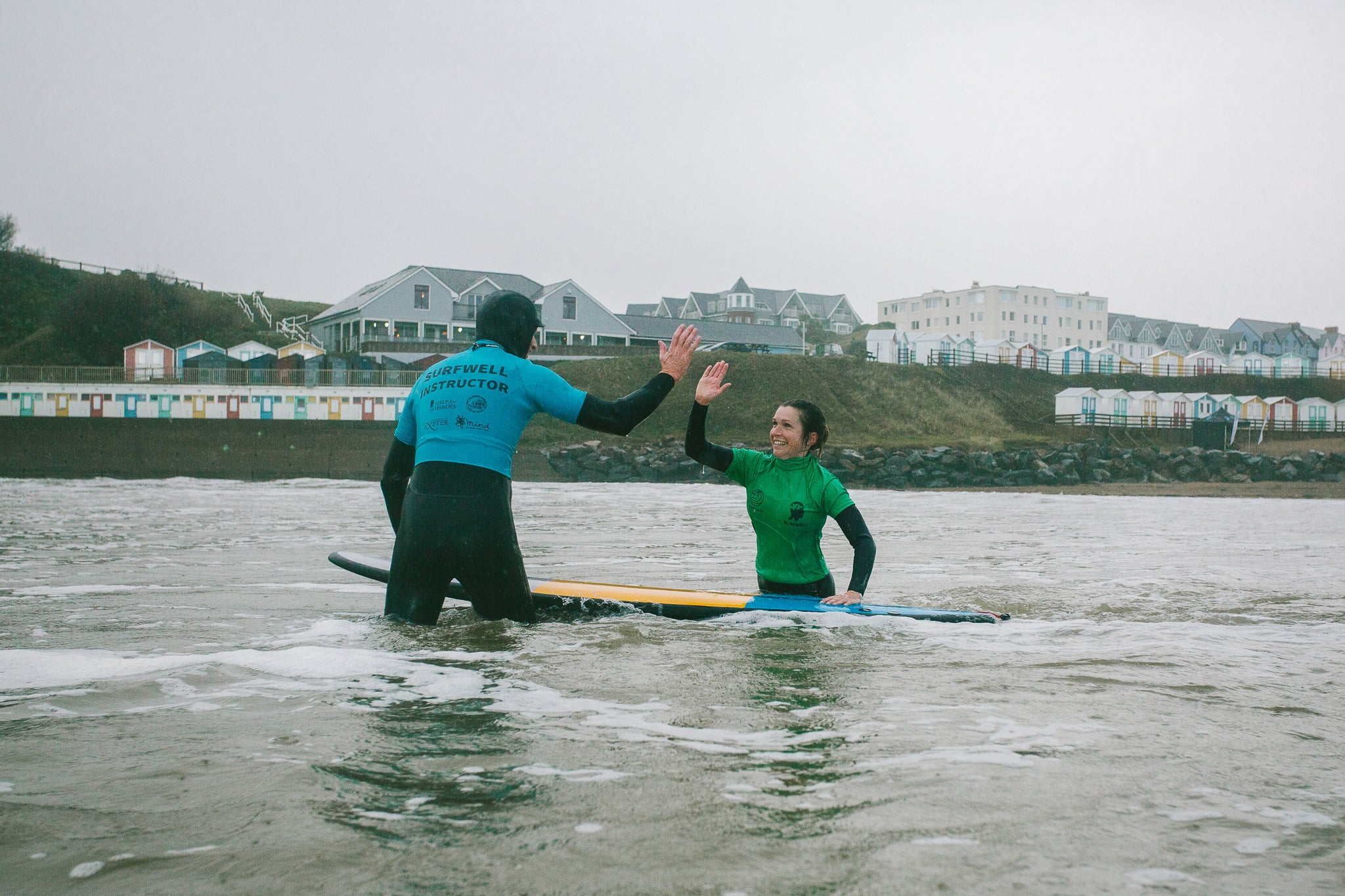 Surfwell participant and a surf therapy instructor giving each other a high-five in the water