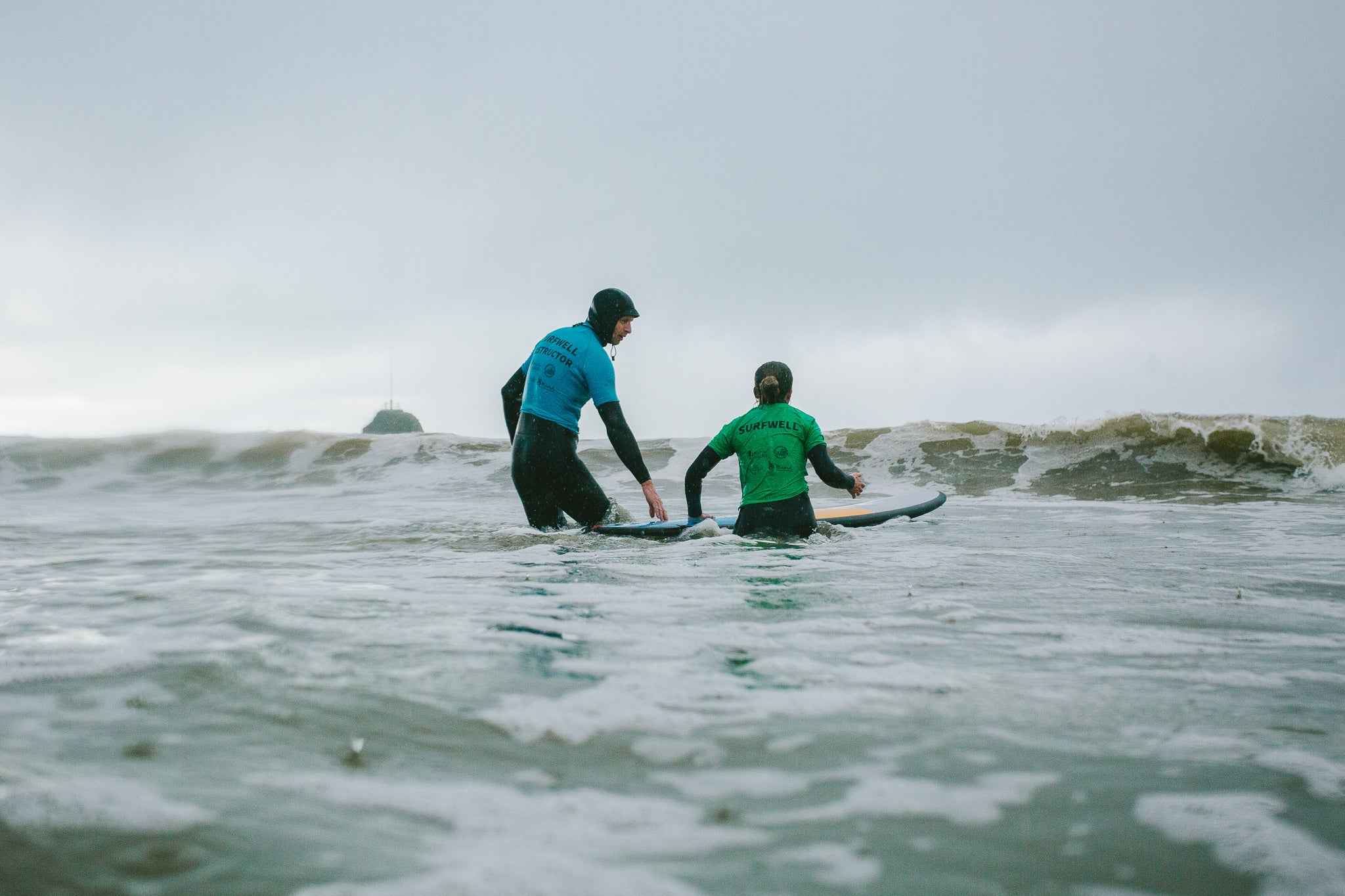 Surf therapy instructor in the water with a Surfwell participant