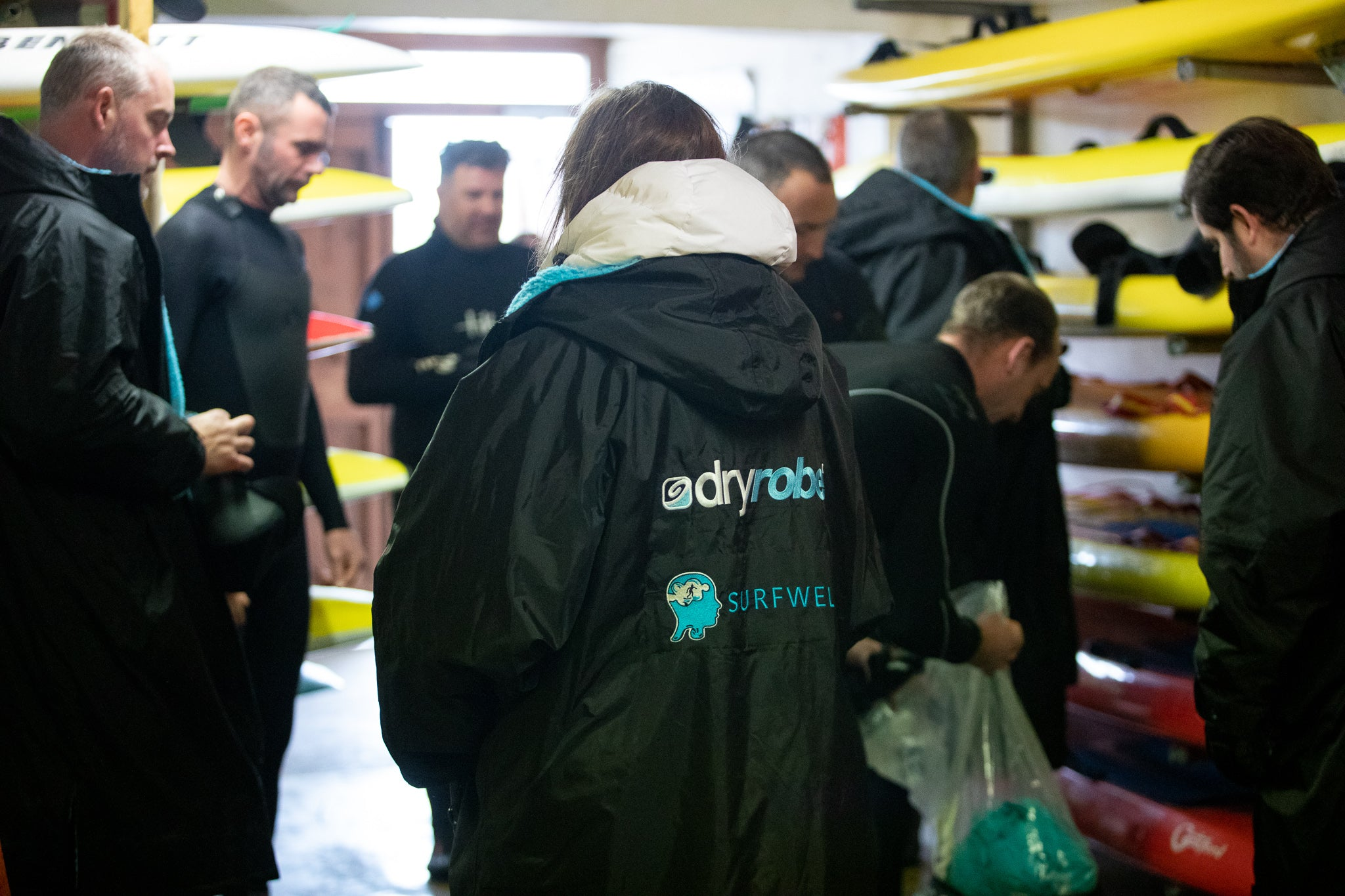 Surfers getting their boards ready indoors wearing dryrobes