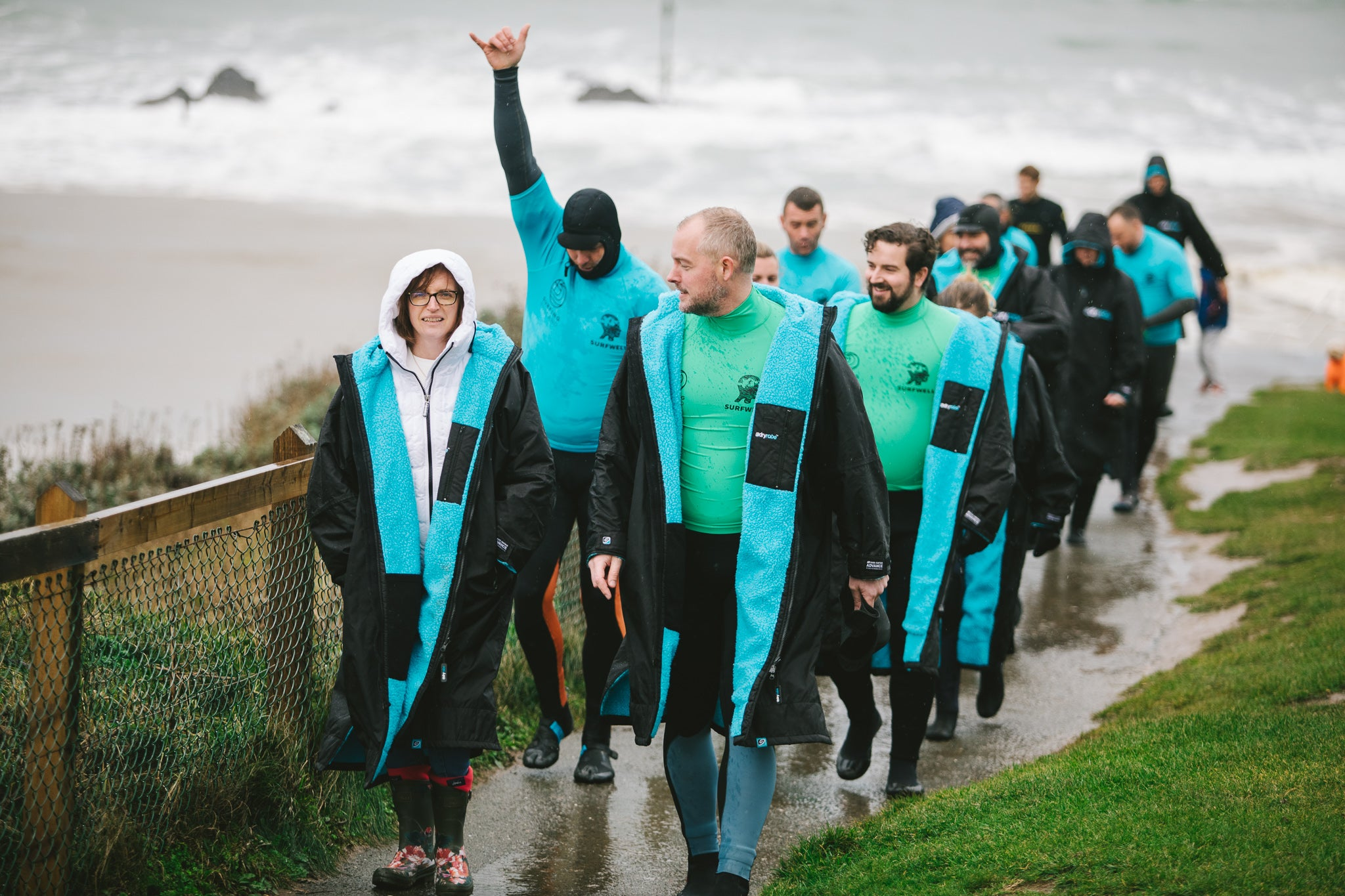 Surfwell surf therapy participants walking from the beach wearing black and blue dryrobes