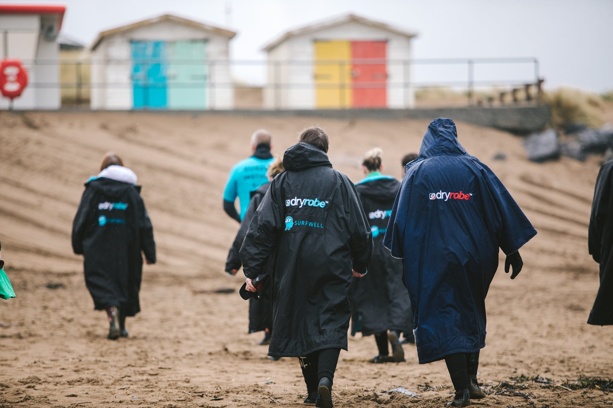 Surfers wearing dryrobes on the beach walking towards beach huts