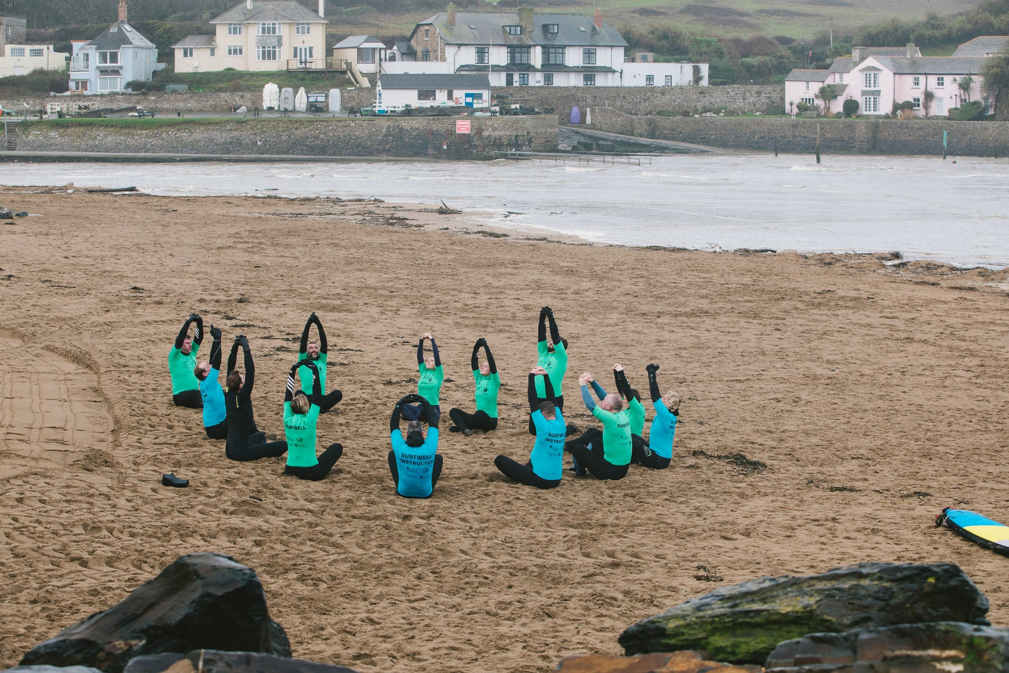 Surfwell surf therapy participants stretching on the beach