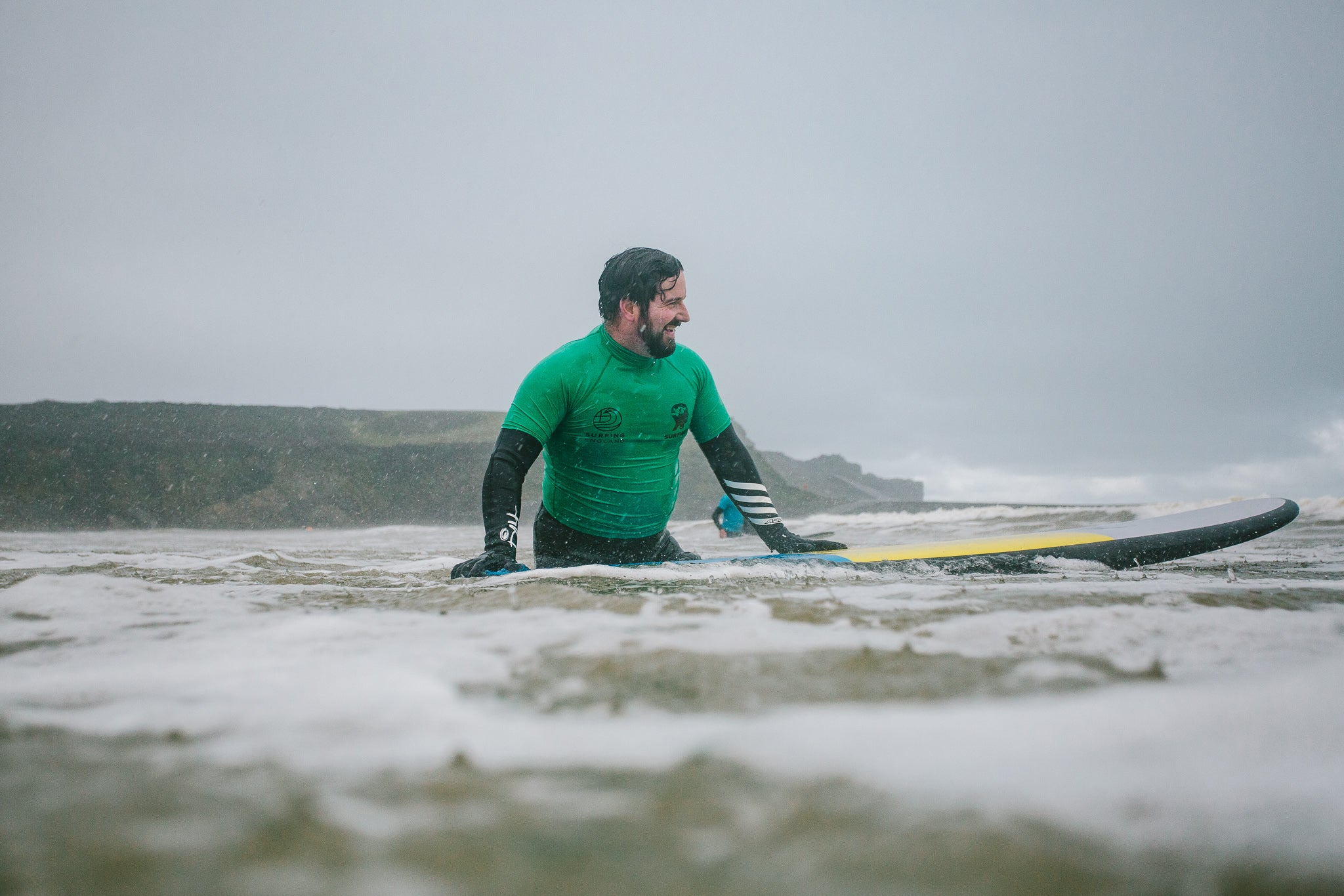 Surf instructor in the water holding a surfboard