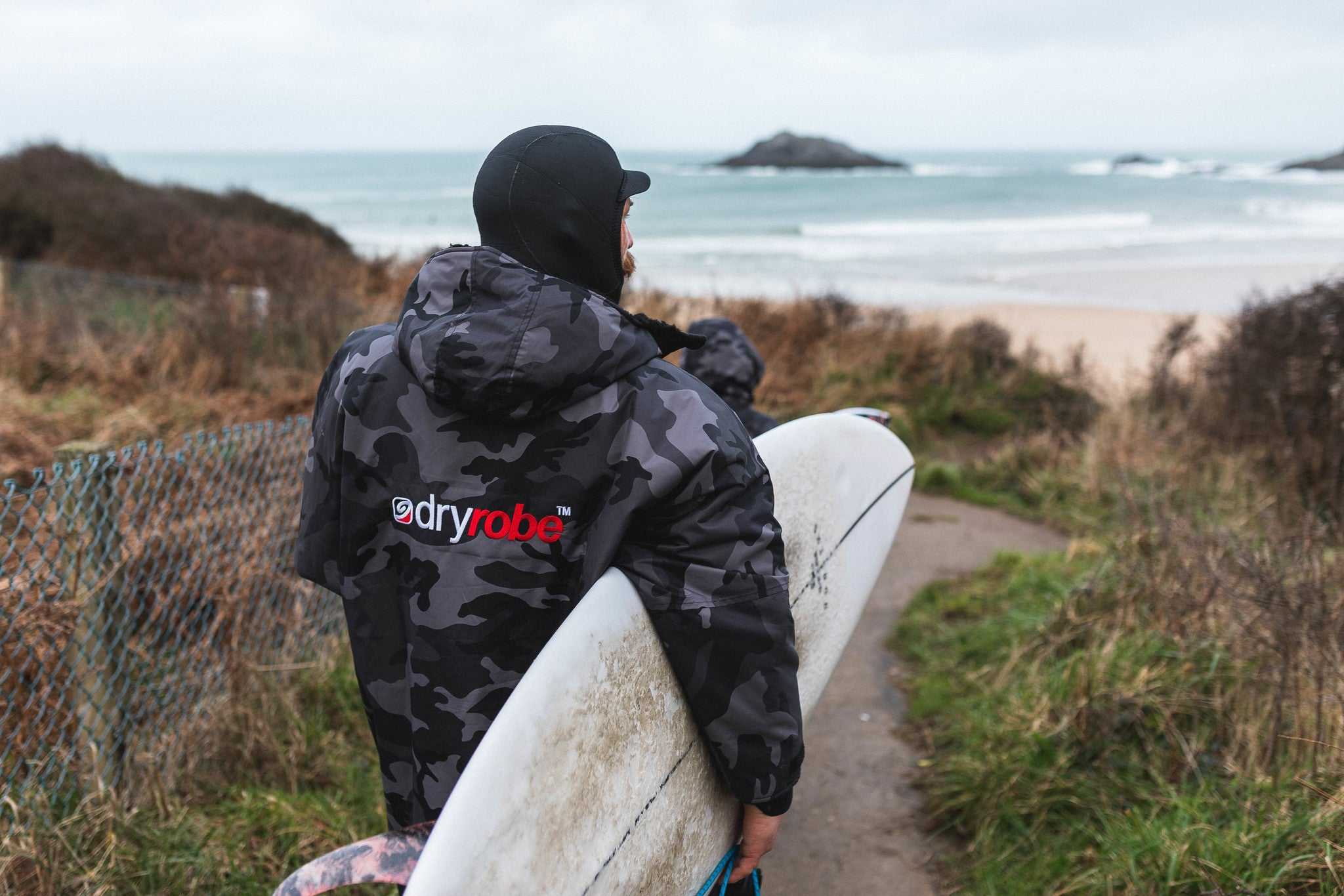 Ben skinner carry his surfboard to the beach whilst wear a Camo Black dryrobe Advance