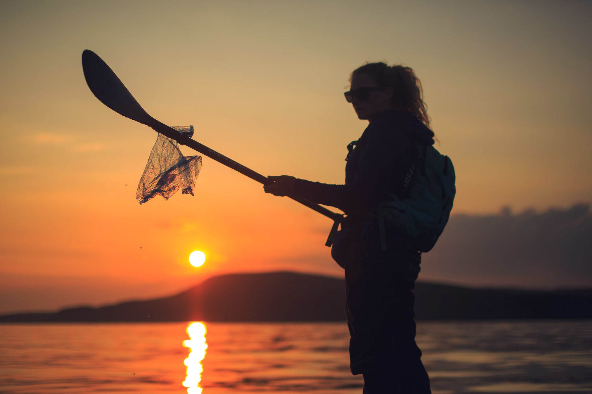 Cal Major collecting rubbish from the sea with her paddle