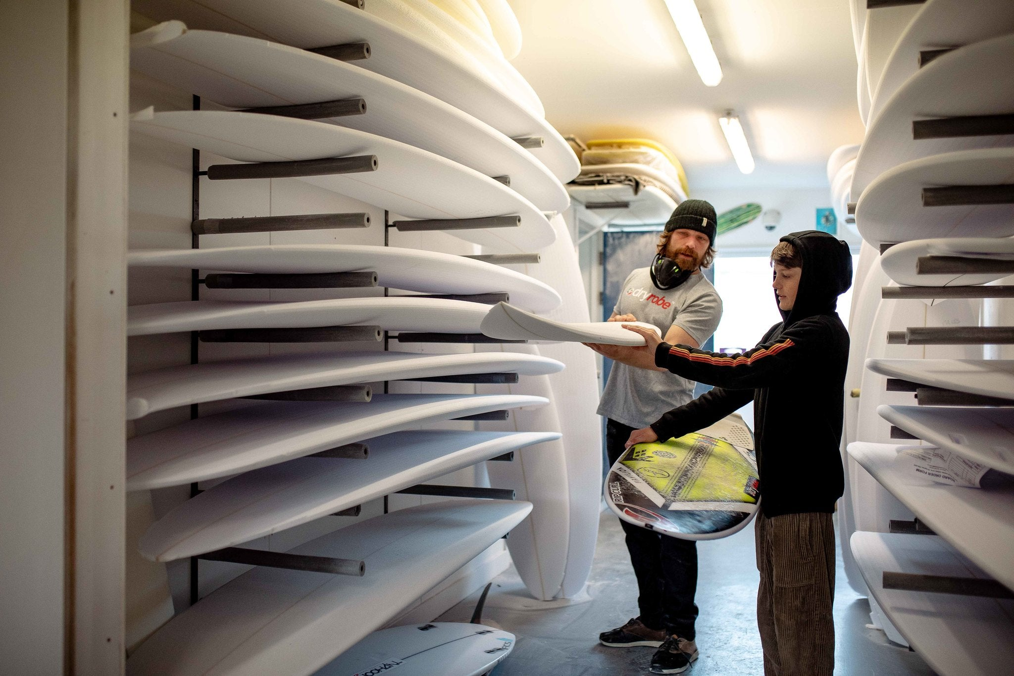 Ben and Lukas Skinner looking at surfboards